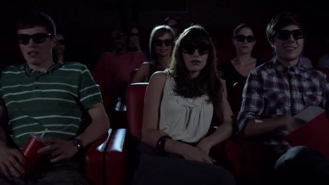 vídeos de stock, filmes e b-roll de young people watching 3d movie at the movie theater - óculos de terceira dimensão