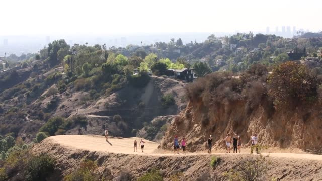 Young people wearing athletic gear walk the dirt paths around Hollywood Hills Three young women wearing sports bras and shortshorts stop to take...