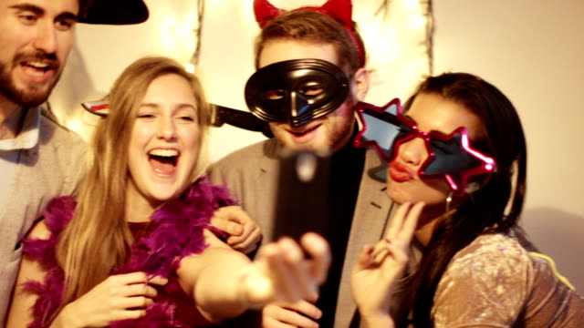 Young people wearing funny costumes and taking selfie at a party