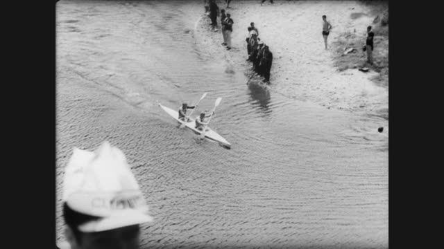 vidéos et rushes de young people with flower leis around their neck hop on train / aerial view of contestants going down river in kayaks and crowd standing on the... - concurrent