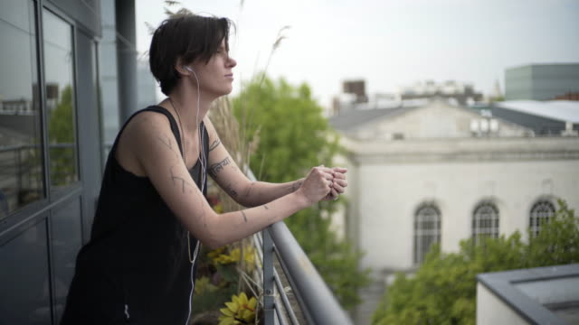 A young person on a city balcony listening to a podcast.