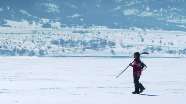 young person walking through snow with hockey gear. - equipment stock videos & royalty-free footage