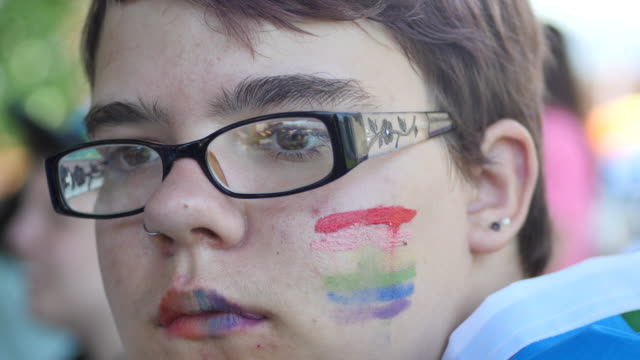 young person with gay pride rainbow flag colors on their cheek, during spencer pride, saturday, june 3, 2017 in spencer, indiana. the festival, open... - diritti lgbtqi video stock e b–roll