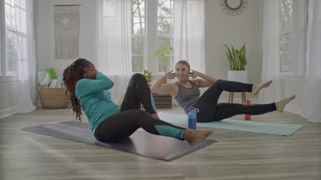 young personal trainer leads african american woman in bicycle crunches in home yoga studio. - washboard stock videos and b-roll footage