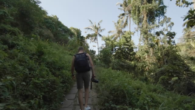 young photographer exploring bali - fotografo video stock e b–roll