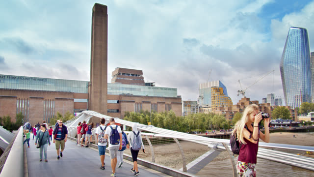 young photographer takes picture near tate modern art gallery. people walk by on elevated walkway. - week stock videos & royalty-free footage