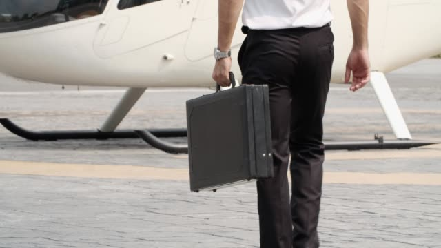 young pilot holding a suitcase and walking to helicopter - conformity stock videos & royalty-free footage