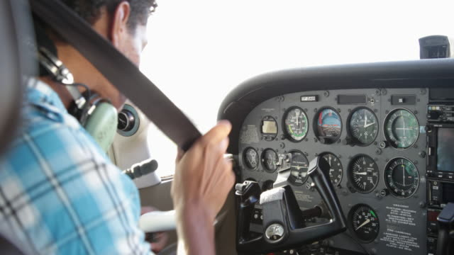young pilot in cockpit preparing to fly private airplane - karibik stock-videos und b-roll-filmmaterial