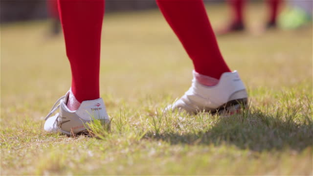Young player with red socks and white cleats stands ready and kicks ball on Brazilian soccer field