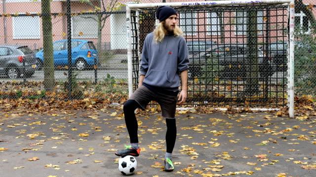 vidéos et rushes de jeune joueur avec ballon de foot contre le poteau de but - terrain de sport sur gazon