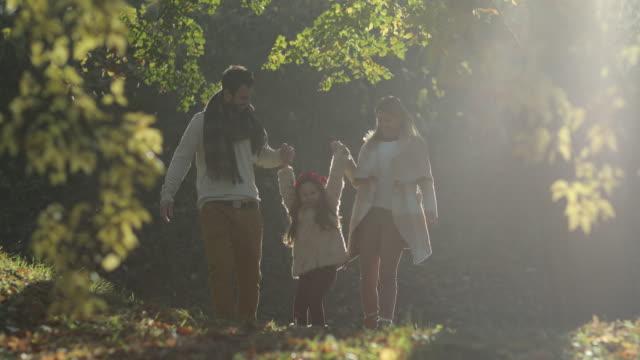 junge verspielte eltern spaß mit tochter im herbst park. - public park stock-videos und b-roll-filmmaterial