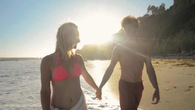 MS TD TU POV TS Young playful romantic couple walking together on beach at sunset / Malibu, California, United States