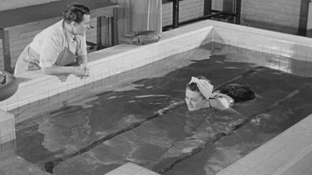1949 MONTAGE Young polio paralysis patients receiving physical and aquatic therapy with the aid of hand rails and indoor pool / United Kingdom