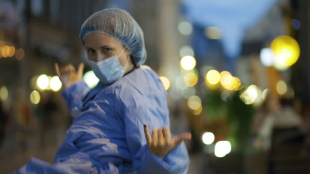 young positive medical student, doctor or nurse dances in city centre - surgical cap stock videos & royalty-free footage