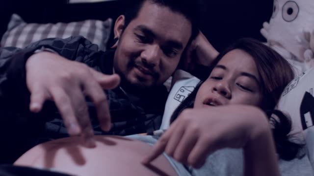 Young pregnant couple in bed.