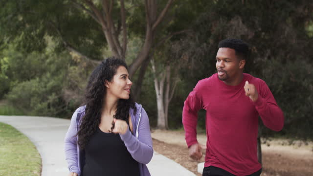 young pregnant couple walking in the park - outdoors stock videos & royalty-free footage