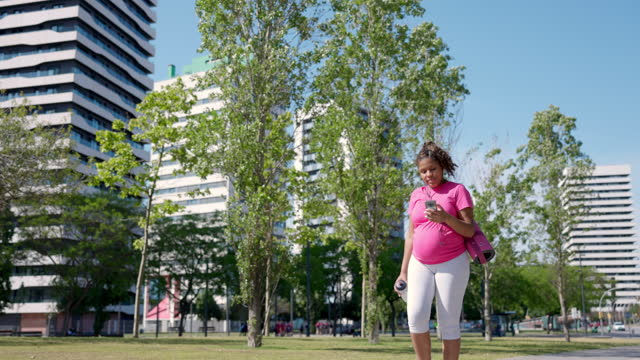 young pregnant hispanic woman walking and listening to music - maternity wear stock videos & royalty-free footage