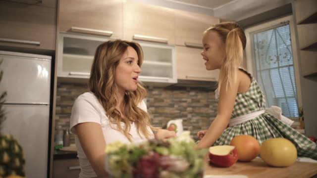 Young pregnant mother and her small daughter eating a healthy snack in the kitchen and talking.