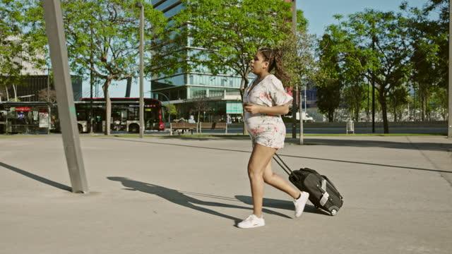 vídeos y material grabado en eventos de stock de joven viajera embarazada corriendo con equipaje con ruedas - urgencias