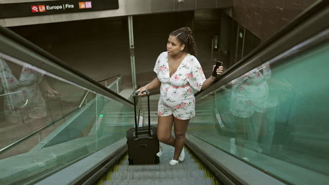 young pregnant vacationer moving up escalator with suitcase - maternity wear stock videos & royalty-free footage