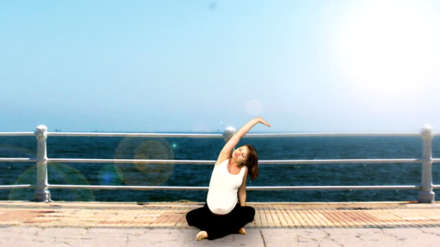 A young pregnant woman does yoga on a platform in front of the ocean.