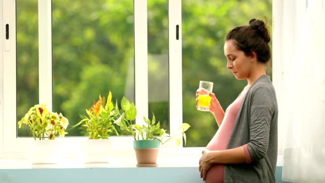 ms young pregnant woman drinking orange juice while standing near window / chhatarpur, delhi, india - orangensaft stock-videos und b-roll-filmmaterial