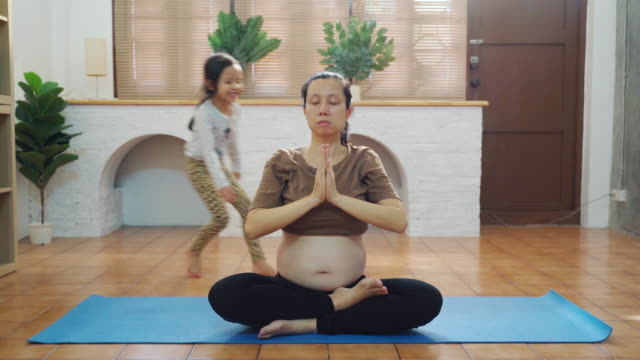 young pregnant woman exercise yoga pose while daughter playing in living room - exercise room stock videos & royalty-free footage
