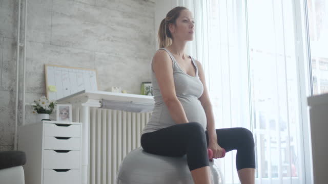 young pregnant woman exercising at home. - fitness ball stock videos & royalty-free footage