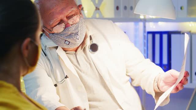 covid-19パンデミック中に病院で女性の相談について男性医師と話し合っている若い妊婦。保護フェイスマスクを着用してカーブを平らにする。新しい法線。医院での医師患者相談。 - 産科医点の映像素材/bロール