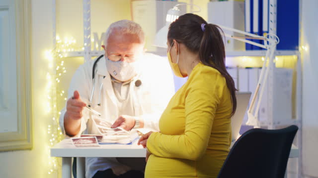 a young pregnant woman having a discussion with her male doctor on a female consultation in the hospital during covid-19 pandemic. wearing protective face masks to flatten the curve. the new normal. doctor patient consultation in a medical clinic. - pregnant stock videos & royalty-free footage