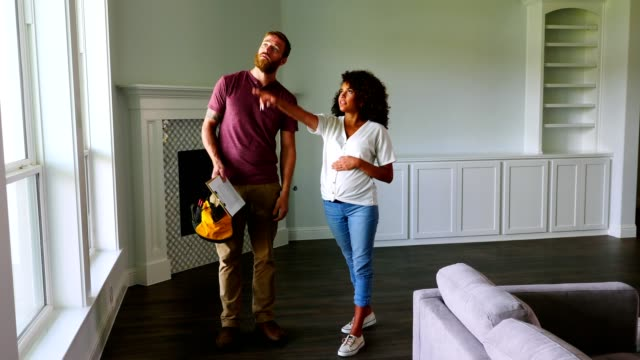 young pregnant woman talks with contractor in new home - home ownership stock videos & royalty-free footage