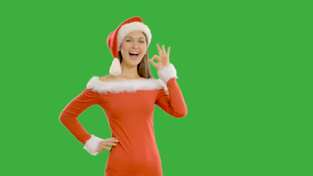 Young pretty girl shows copy space in santa claus hat