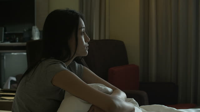 4k: young pretty lonely sad girl sitting on sofa and hugging her knees - depression sadness stock videos & royalty-free footage