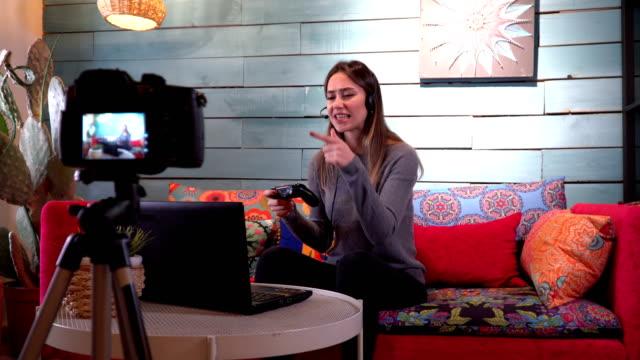 stockvideo's en b-roll-footage met jonge mooie pro gamer hebben live streamen en spelen in online video game bij het opnemen van dagelijkse vlog - commentator