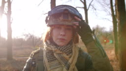 Young pretty redhead woman in military uniform armed with rifle at the battlefield area