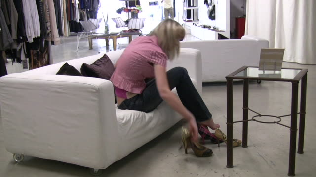 young pretty woman shopping at modern  boutique  shoe - mid length hair stock videos & royalty-free footage