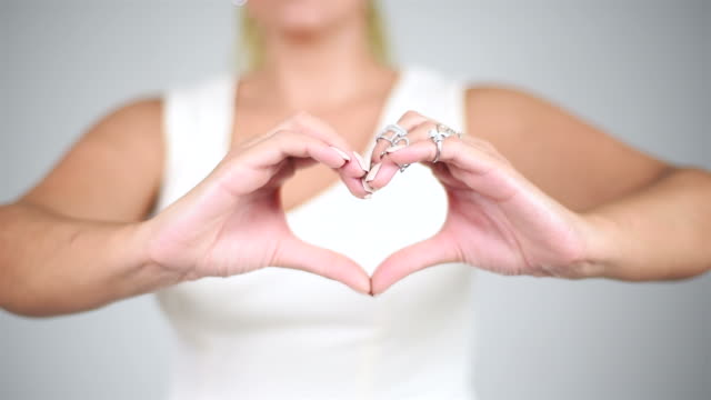 Young pretty woman showing heart with her fingers on isolated grey background.