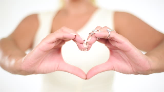 Young pretty woman showing heart with her fingers on isolated white background.