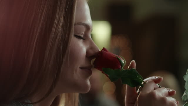 Young pretty woman smelling red rose