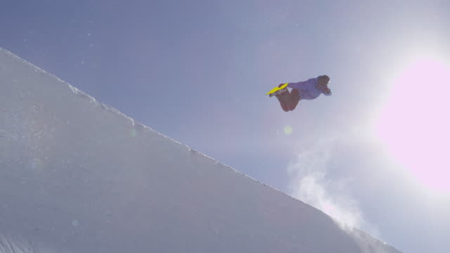 SLOW MOTION: Young pro snowboarder jumping in half pipe in sunny snow park