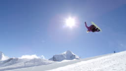 SLOW MOTION: Young pro snowboarder jumping over the sun in half pipe snow park