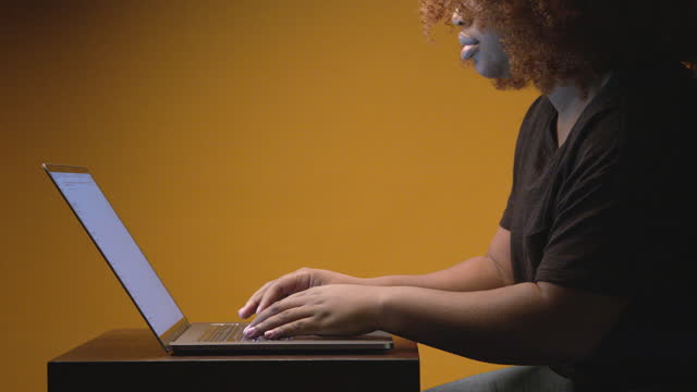 young professional african american woman sitting and typing on a laptop computer under dramatic lighting in front of a yellow mustard colored studio background with copy space - color negro stock videos & royalty-free footage