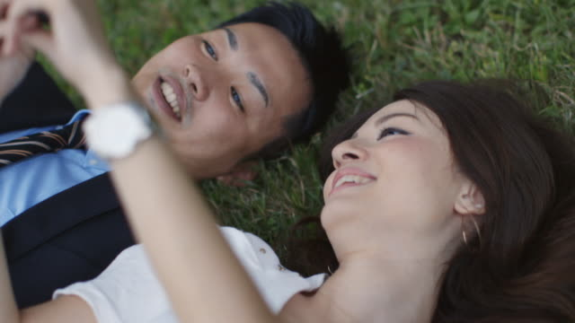 CU, HA Young, professional couple lie in grass looking up at mobile phone / Tokyo, Japan