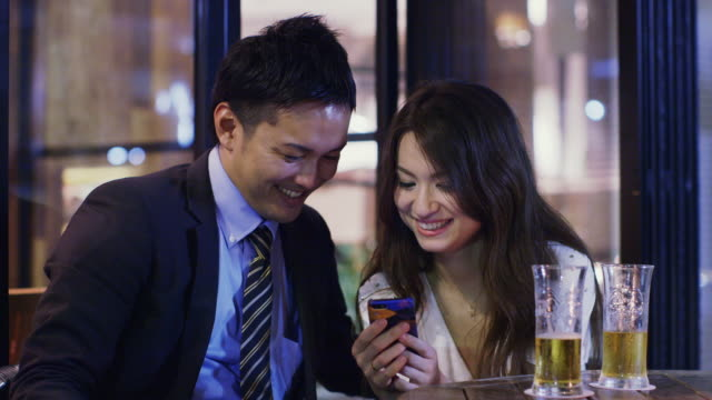 ms young professional couple look at mobile phone and laugh in a bar / tokyo, japan - 見せる点の映像素材/bロール