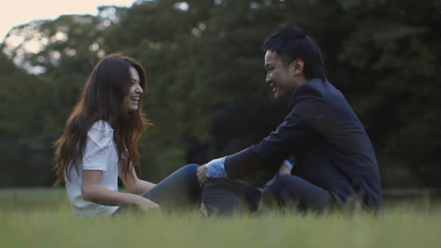 ms, la young, professional couple talk and laugh in the park / tokyo, japan - デート点の映像素材/bロール