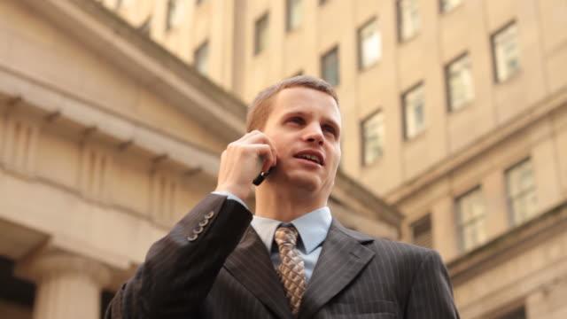 vídeos de stock e filmes b-roll de a young professional man talks on his cell phone outside. - olhar em redor