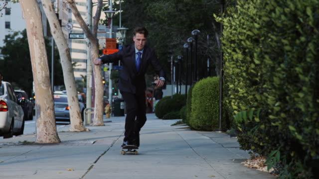 young professional on skateboard - 全身点の映像素材/bロール