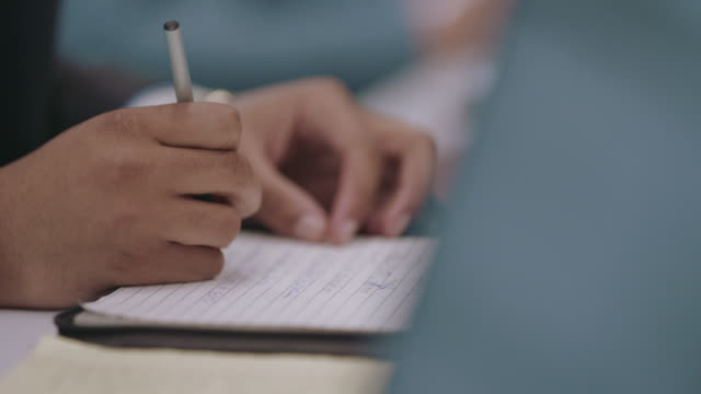 cu young professional quickly writes down notes on a notepad - composition stock videos & royalty-free footage