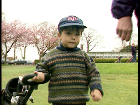 birmingham warley ext 4yearold robert aldred along pulling golf trolley at golf club with father bob robert and father onto tee at golf club robert... - golf bag stock videos and b-roll footage