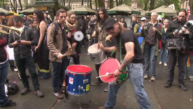young protesters bang on drums at the may day occupy wall street rally in bryant park nyc - bryant park stock videos and b-roll footage
